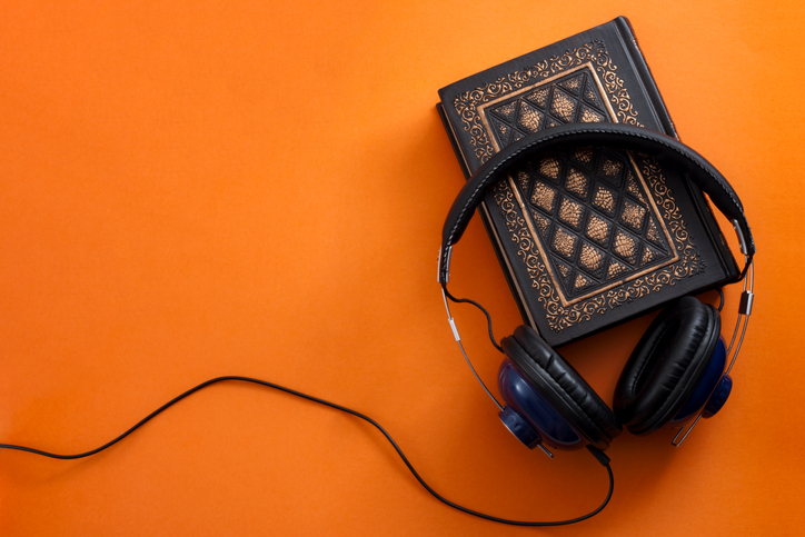 Headphones and a vintage book against an orange background