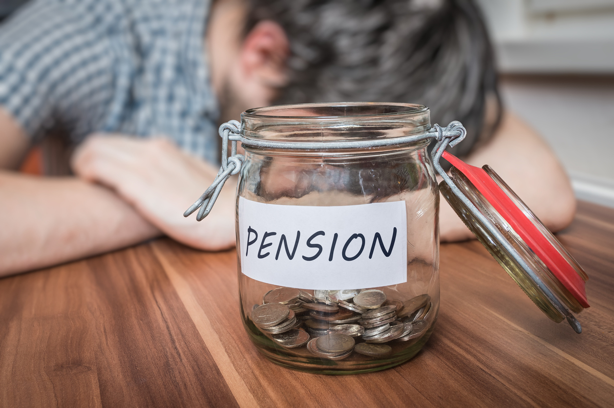 Depressed man lying on table worried about pensions. A pension savings in jar in front.