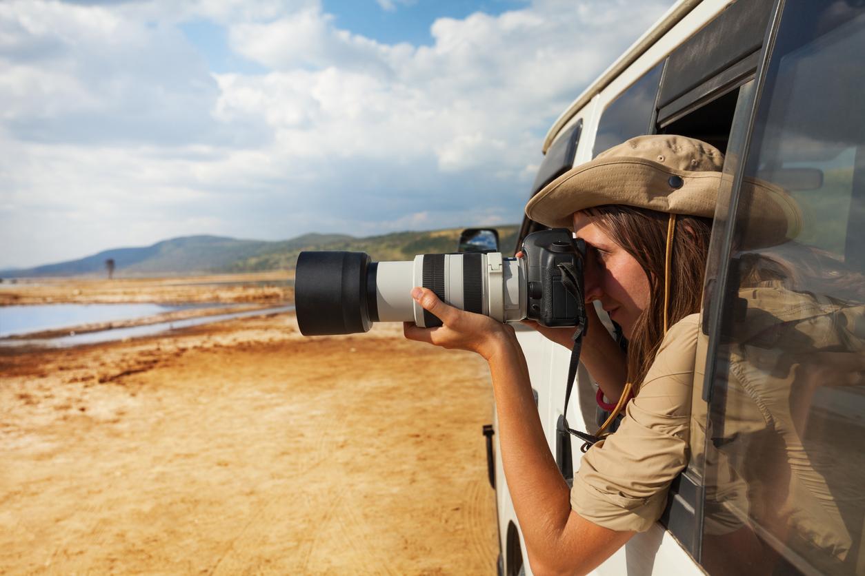 Side view portrait of young woman taking photo of Kenyan lake Nakuru from the open window of safari jeep