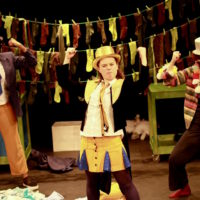 Daisy stands in the centre of the stage with her arms held up, her hands in fists. The general colour scheme of the photo is black, dark red, brown and yellow, as Daisy has long washing lines of socks in these colours hanging up behind her. She is wearing a yellow top hat, black suit jacket with tails and yellow denim skirt with blue glittery pleats. She also wears a yellow tie over her white shirt and has an expression on her face that suggests she is ready to fight. Her friends stand behind her on either side. The friend on our left looking at the image is also wearing a white shirt and simple suit jacket but with a blue tie and orange trousers. The friend on the right of the image is wearing an outfit all in black apart from a multi-coloured and pom-pom decorated cardigan. Both friends are wearing cream top hats. Around them, strewn on the floor, is a mess of what looks like clothes, fabric and toys.
