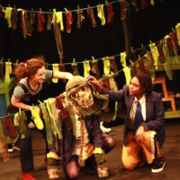 One of the washing lines of yellow, brown and red socks stretches diagonally forward across the stage and Daisy crouches behind it. Her friends are on either side of her, holding up a patchwork monkey puppet face over Daisy's. Daisy has one hand up on the washing line but the other is on the floor, covered in a patchwork monkey paw.