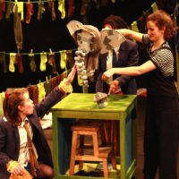 Daisy's friends are acting as puppeteers for a patchwork elephant puppet's head and front two feet. On top of a green table, with a stool folded underneath, is the elephant and Daisy is crouching in the bottom left corner of the image with her left arm outstretched towards the elephant.