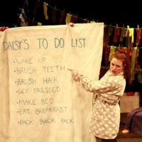 Daisy stands on the right of the image with her hair in a messy ponytail, tied up with a red scrunchie. She is wearing a grey dressing gown with white hearts on and is angrily pointing at a big sheet that is held up, listing her 'To Do List.' She is pointing to the second on the list, 'Brush Teeth,' which comes after 'Wake Up' and is followed by 'Brush Hair,' 'Get Dressed,' 'Make Bed,' 'Eat Breakfast' and 'Pack Back Pack.'