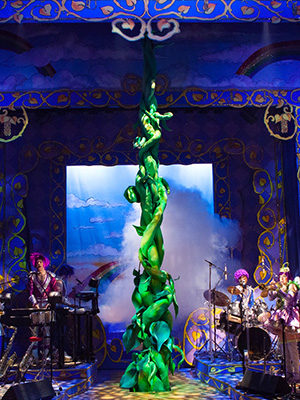 A royal blue set with gold vines spiraling around the borders, actor-musicians stand either side of a large green beanstalk twisting up from the centre of the stage beyond the lights above. White smoke is billowing out from behind it.