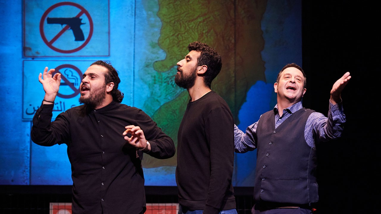 Three men stand in a line, facing the left of the image. The first is creating an 'O' shape with his thumb and forefinger on both hands and looks like he is trying to explain something in a serious manner. The middle man is standing with his hands by his sides, looking exasperated. The final man, on the right, is gesturing towards the audience, the hint of a smile on his face and his left arm stretched open. Behind them is a large map on the wall and two signs banning weapons and smoking.