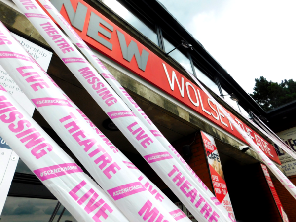 A zoomed-in image of four strands of white tape reading 'Missing Live Theatre' and '#SceneChange' in pink text, suspended from the first floor of the New Wolsey Theatre to the ground outside. The sign on the front of the building that reads 'New Wolsey Theatre' is the background of the image.