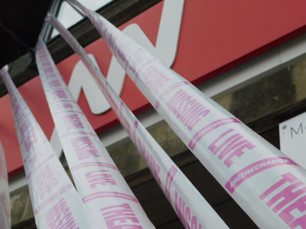 A zoomed-in image of four strands of white tape reading 'Missing Live Theatre' and '#SceneChange' in pink text, suspended from the first floor of the New Wolsey Theatre. The New Wolsey logo on the front of the building is the background of the image.