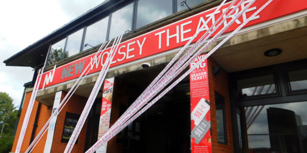 The front of the New Wolsey Theatre decorated with the pink and white tape of #SceneChange, which is zig-zagging from the first floor to the ground outside and up again.