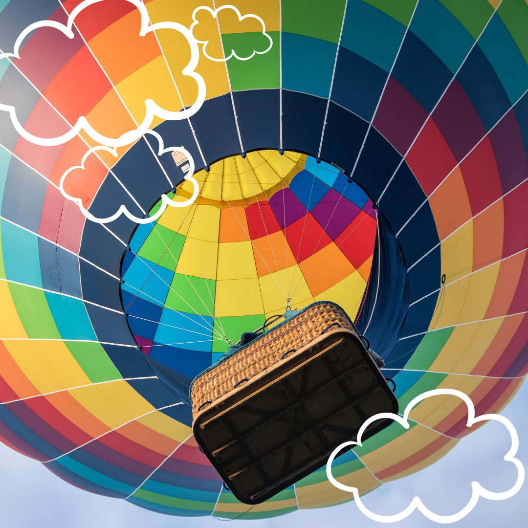 The image shows a photograph of a colourful hot air balloon in the sky from below, three white clouds that look illustrated dotted across the top left and bottom right corners of the picture.