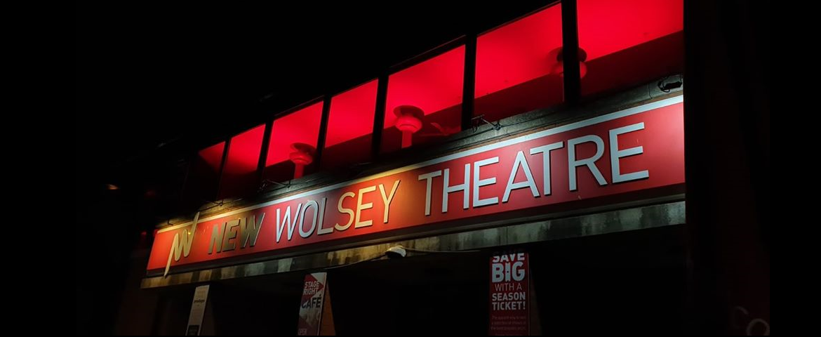 The image shows the front of the New Wolsey Theatre at night, with the inside of the building lit up in red light. The large 'New Wolsey Theatre' sign above the doors runs across the image.