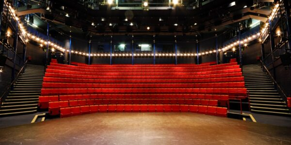 Photograph by Carl Lamb. The image shows an empty New Wolsey auditorium, from the stage, looking out towards the seats. There is no set on the stage and the room is lit up as if before a show.