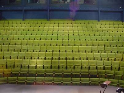 The image shows the view of the New Wolsey auditorium seats from the stage, all empty and a bright lime-green in colour.