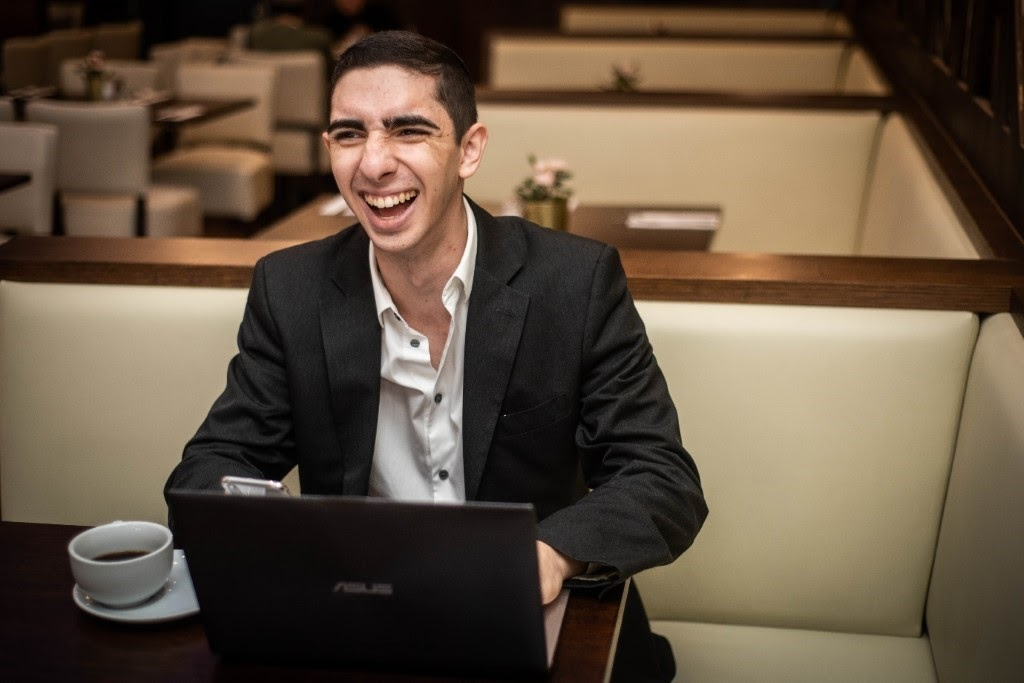 A person sitting at a table with a computer and smiling at the camera  Description automatically generated