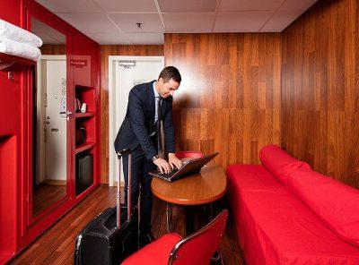 Pukumies tekemässä töitä läppärillä Omenahotellin huoneessa