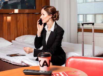 Helsingin Omenahotellissa työmatkalla oleva nainen istumassa sängyllä
