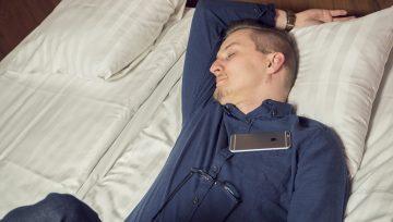 Kuva miehestä nukkumassa hotellin sängyllä
