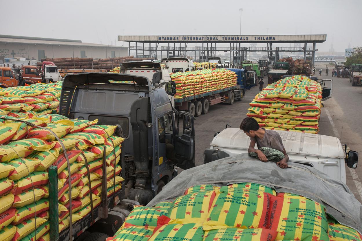 Truckers wachten voor de toegangspoorten van Thilawa. Hun vrachtwagens zijn volgeladen met rijst en hout.