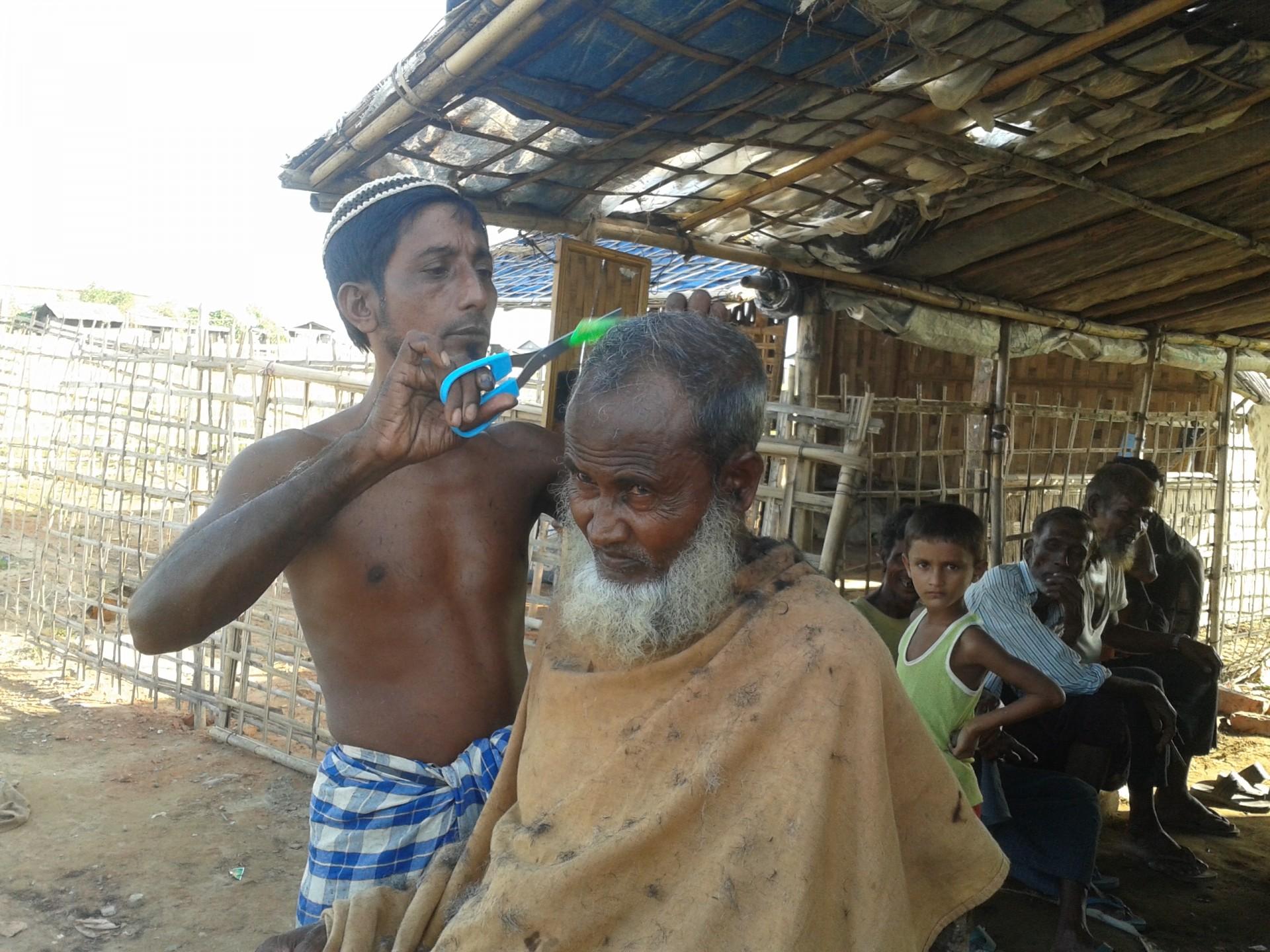 Een oudere Rohingya man laat zijn haar knippen in een vluchtelingenkamp in west-Birma