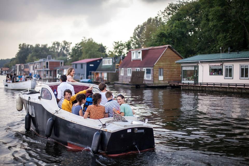 Bewoners van Schoonschip varen langs woonboten