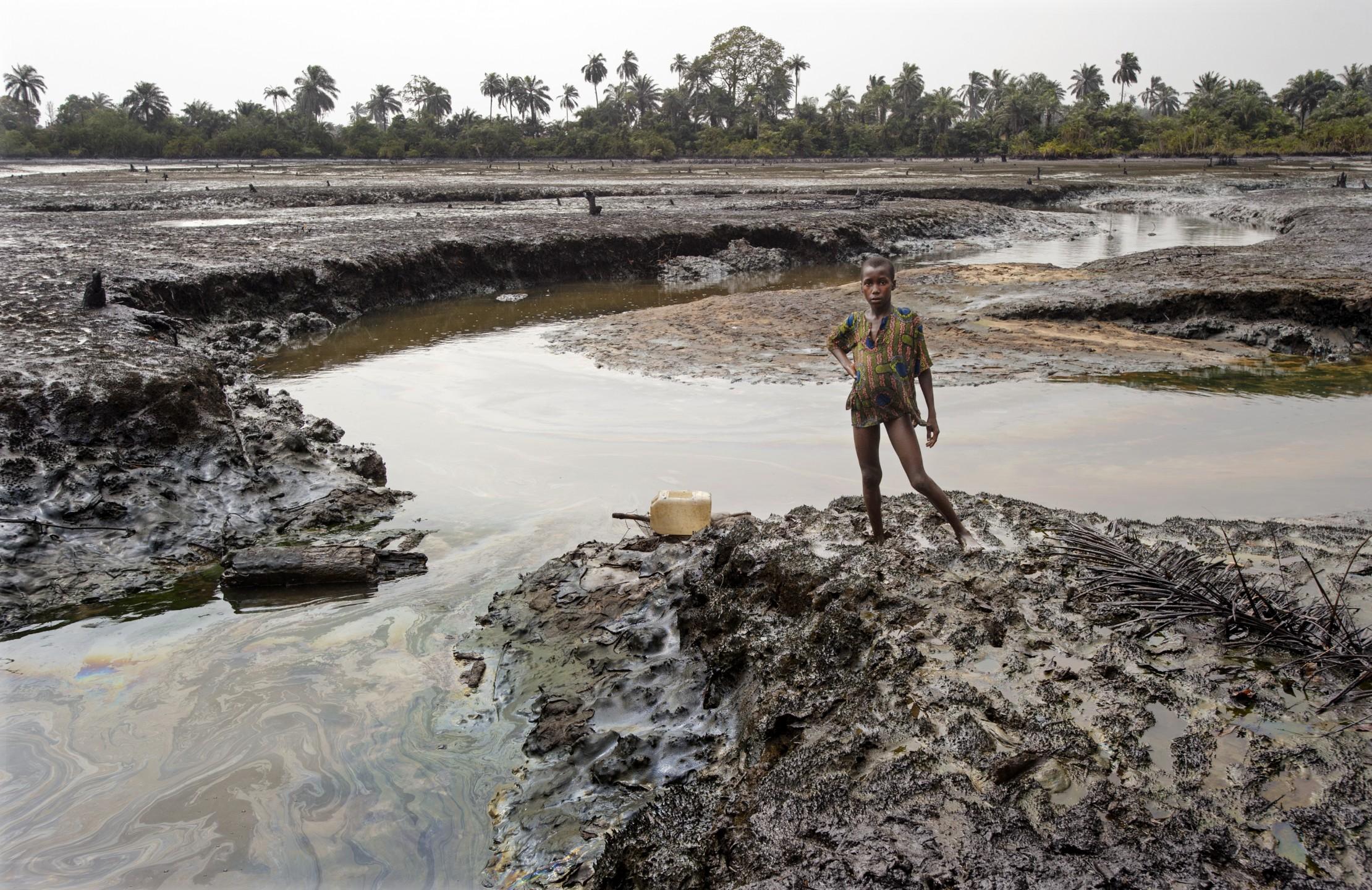 Jongetje staat in met olie besmeurde Nigerdelta, Goi.