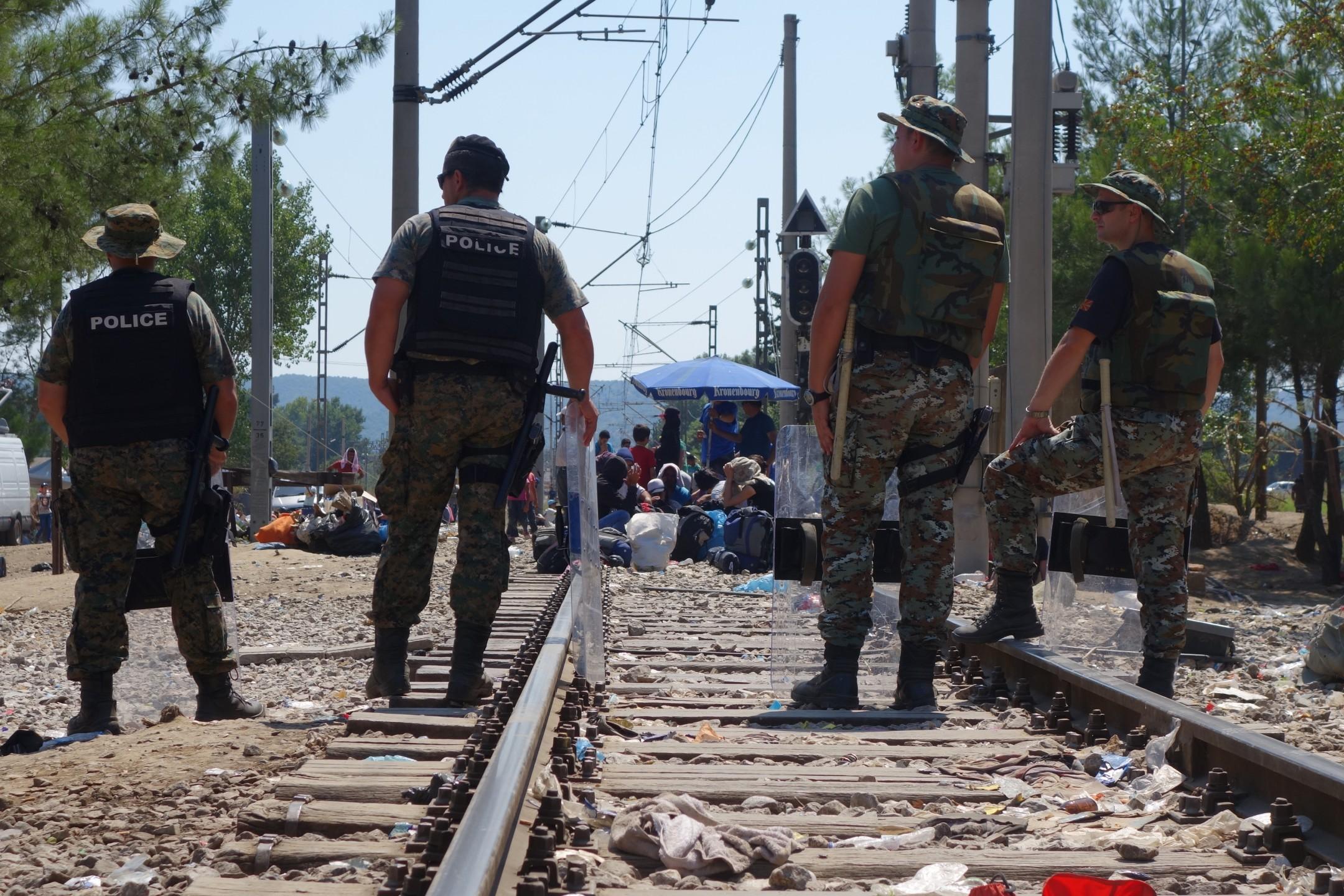 Grenspolitie bewaakt grensovergang tussen Griekenland en Macedonië, waar honderden migranten wachten tot ze door mogen reizen