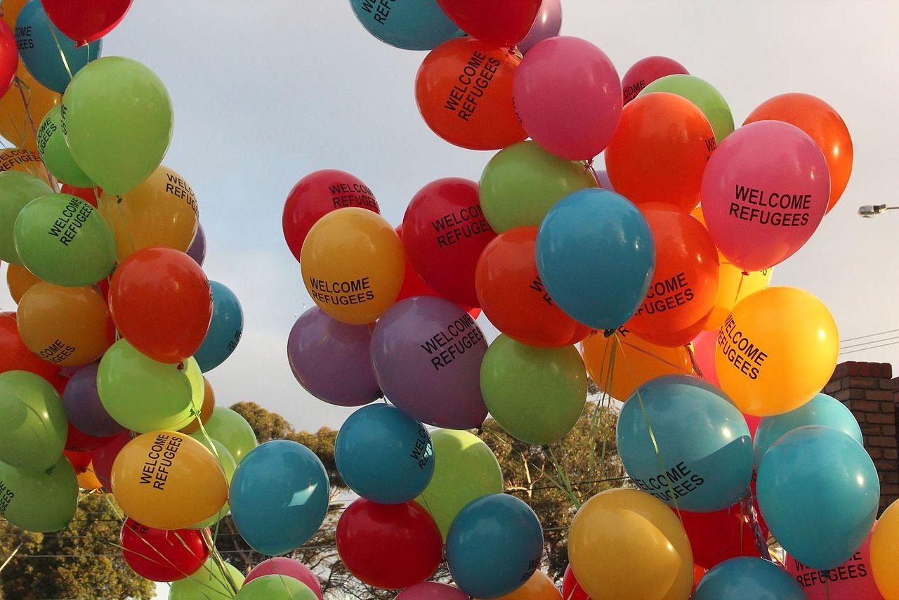 vluchtelingen worden verwelkomd met ballonnen