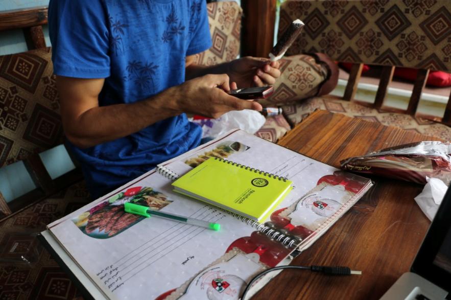 Sardar met het groene notitieboekje, zijn telefoon en een ijsje uit de supermarkt van Shoora