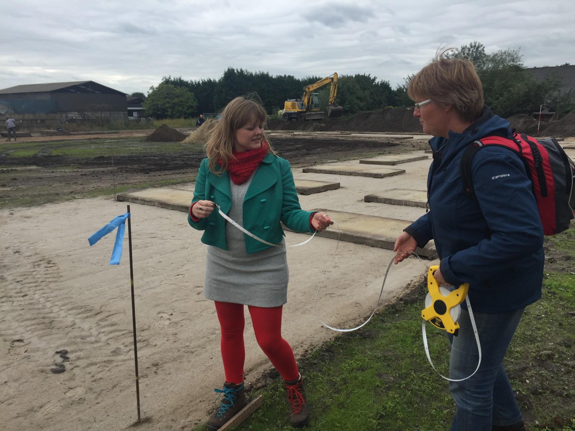Twee vrijwilligers meten de oppervlakte van het dorp om een avonturentuin te maken