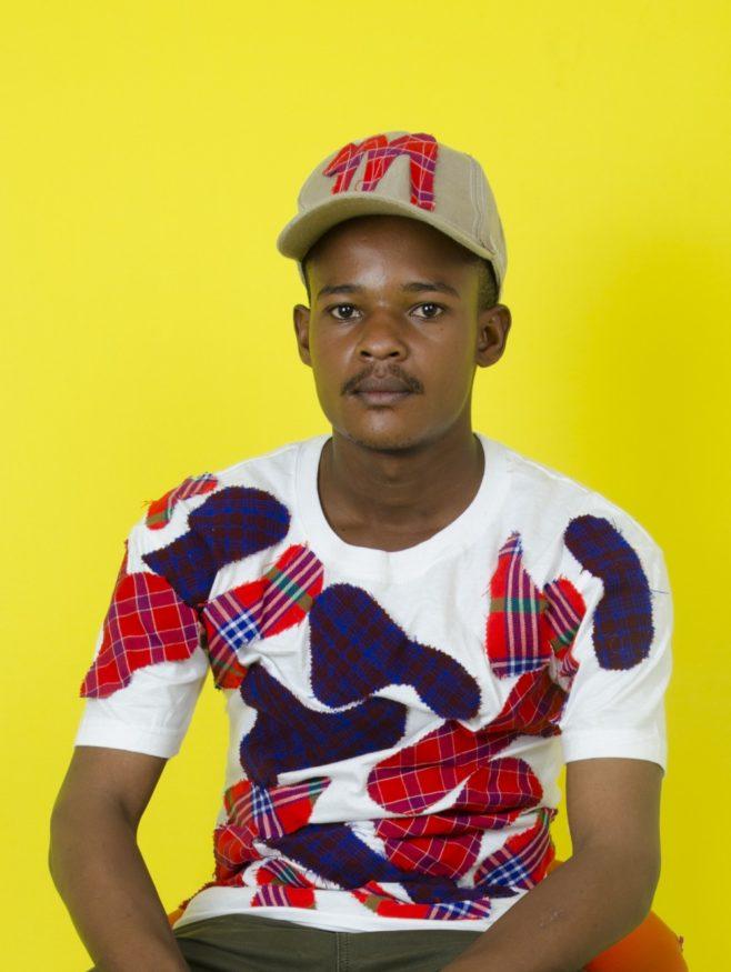Foto: Godlisten, in zijn zelf ontworpen shirt met Masaipatronen.