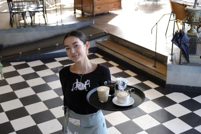 Hoofdkelner Amieke met op het dienblad: latte, flat white en filterkoffie