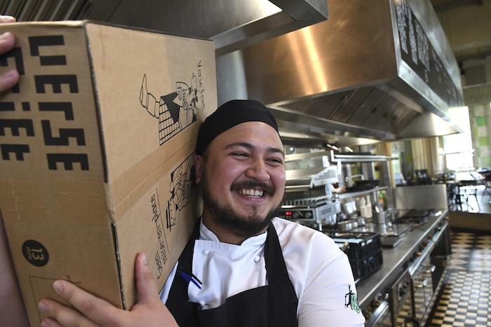 Sous-chef Tim met een levering Friethoes-friet. Tekenaar Joost Swarte ontwierp de huisstijl van de Haarlemse frietbakker