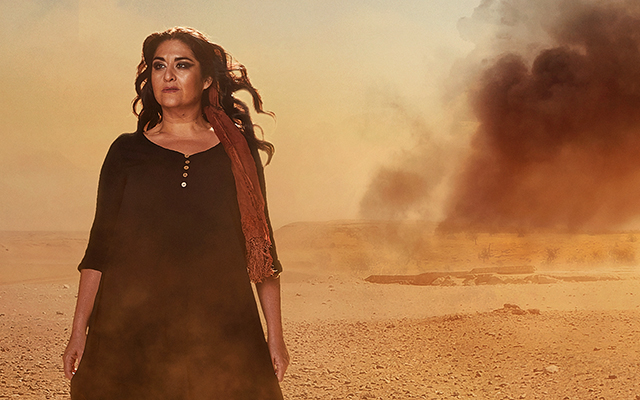 Image showing a woman, Aida, with long dark hair and a black dress is walking barefoot across a desert with black smoke behind her from what looks like bombing