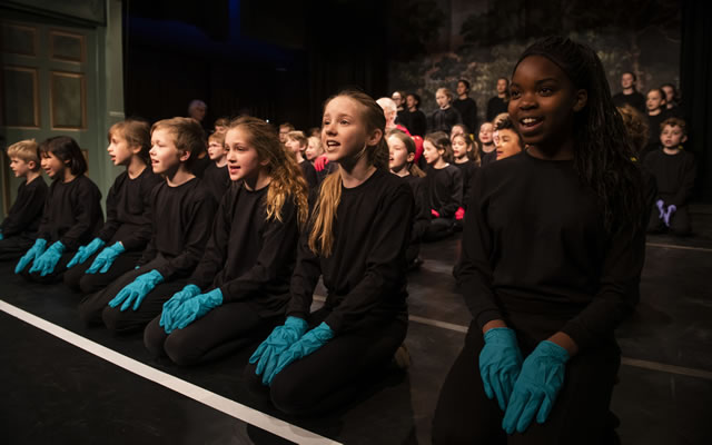 Children wearing black clothesand coloured gloves sit in rows and sing in a performance