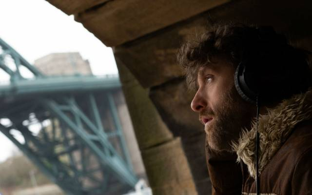 A bearded man wearing headphones and an Afghan jacket, seen in profile under a stone bridge, with a steel bridge visible in the background