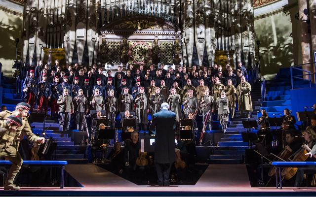 Alex Banfield as Jonathan Dale, Christopher Nairne as William Dale and Rupert Charlesworth as Nikolaus Sprink with the Chorus of Opera North, Students of the Royal Northern College of Music, Opera North Youth Chorus and the Soldiers' Chorus – Community Singers © Tristram Kenton