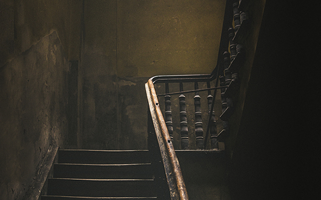 Image showing a dark grimy view looking up the empty stairway of a 1940's Brooklyn tenement building