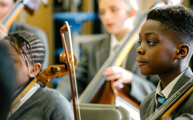 A young member of Opera North's In Harmony education programme holding a violin at a rehearsal