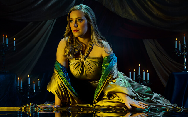 A woman, Cleopatra, dressed in opulent silk clothes leans over a pool of water that reflects her image for Opera North's production of Giulio Cesare
