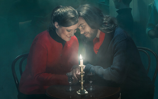 A young couple, Rodolfo and Mimi, sit smiling with their heads resting together and illuminated by candlelight amongst a crowded and smoky bohemian bar in Paris for Opera North's production of La Bohème