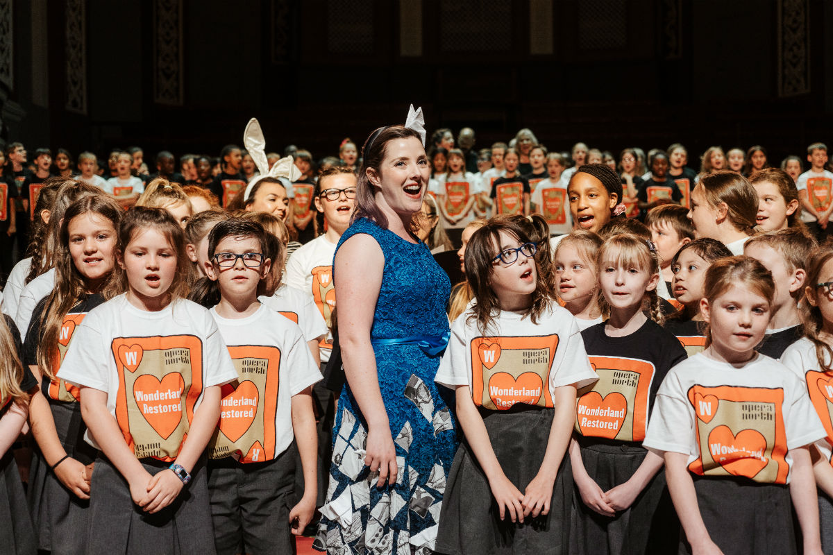 A woman dressed in a bright blue dress sings with a choir of young children dressed in matching white and orange T-shirts