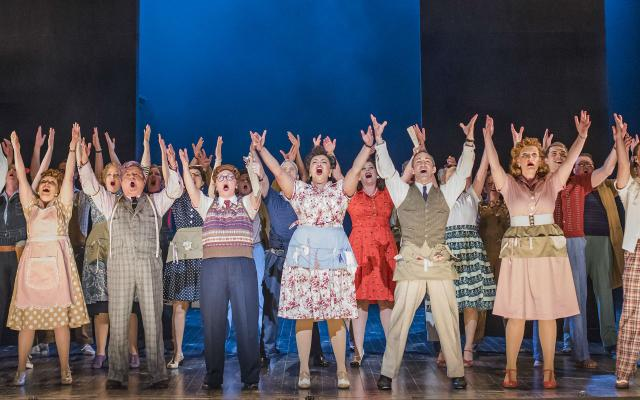 A group stand up-lit and singing passionately with arms upraised in Opera North's production of Kiss Me Kate