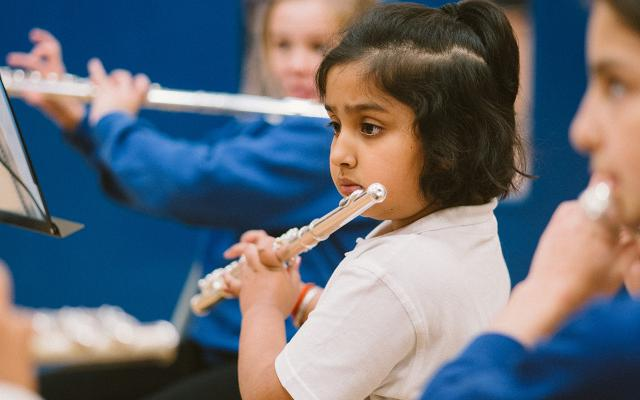 A school child plays the flute as part of Opera North's In Harmony education programme