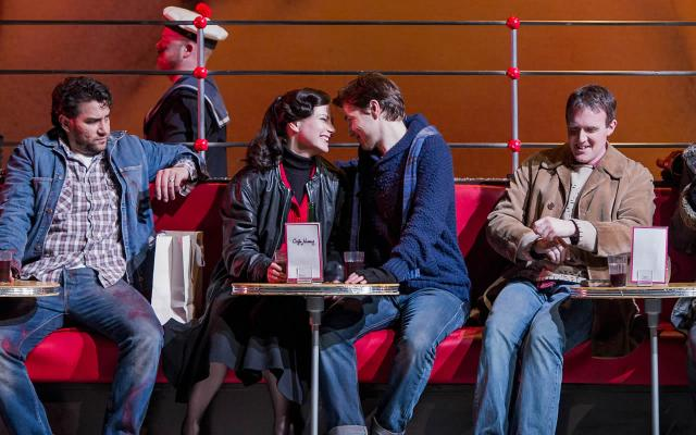 La bohème: A group of friends eat and drink while sat on a red bench