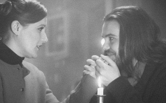 Black and white image of Katie Bird and Thomas Atkins as Mimì and Rodolfo with a candle