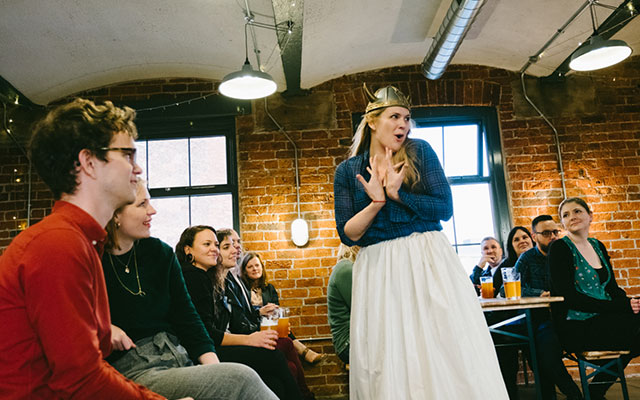 A woman sings with a dramatic stance and in a viking helmet a relaxed setting with a cheerful audience