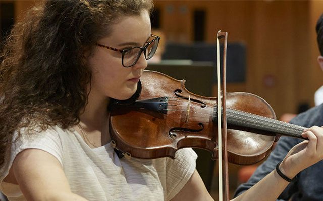 Young musician playing the violin at Opera North's orchestra academy