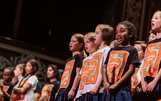 A large group of children wearing matching t-shirts featuring a playing card motif, in an ornate theatre