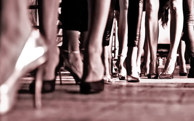 Angled from the ground, a group of women's ankles in high heals