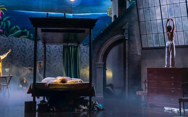 A ghostly scene with a central bed and boy looking out of the window in pyjama bottoms.