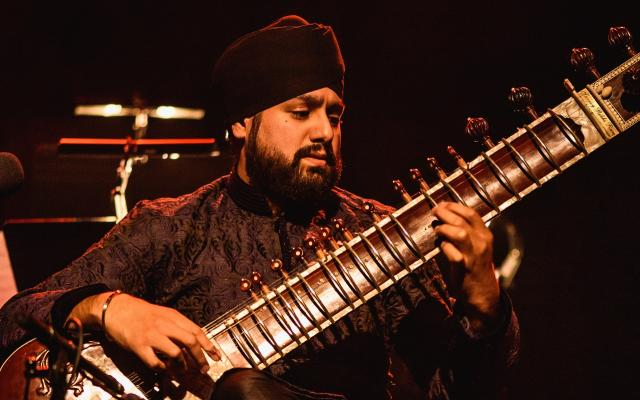 A young Sikh musician plays the sitar on a darkened stage